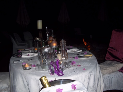 Romantic table setting on deck next to fire