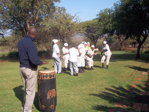 Lodge staff dancing and singing, Nala playing the drum
